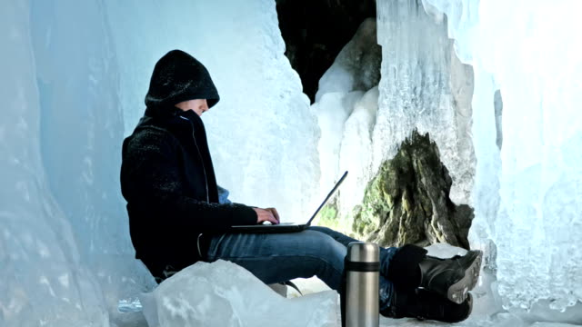 Hacker hacks the server. Man to program on laptop in ice cave. Around the mysterious ice grotto. Man hides himself in a hood. Hacker has criminal cases on the Internet. He's a cool hipster.