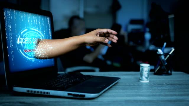 Mano de hacker pasando de monitor de la computadora portátil a robar el dinero sobre la mesa con el tono oscuro y grano procesado por concepto de seguridad de red de cyber - vídeo