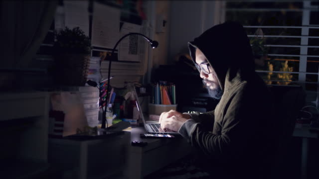 Hacker in hood cracking code using laptop and computers from his dark hacker room video