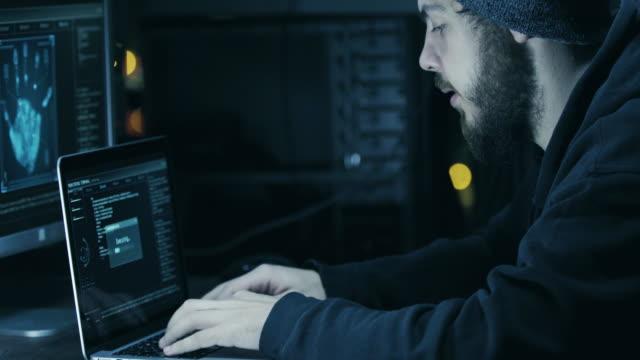 ハッカーのフード亀裂を使用してラップトップとコンピュータハッカー彼のダークルーム - スパイ点の映像素材/bロール