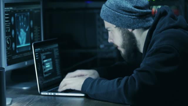 Hacker in hood cracking code using laptop and computers from his dark hacker room video