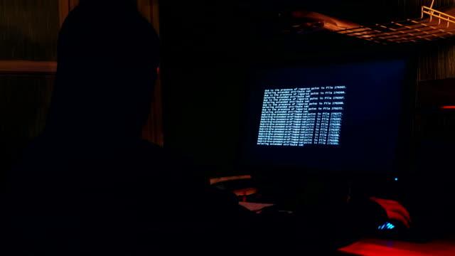 Hacker en la sala frente a un monitor de computadora - vídeo