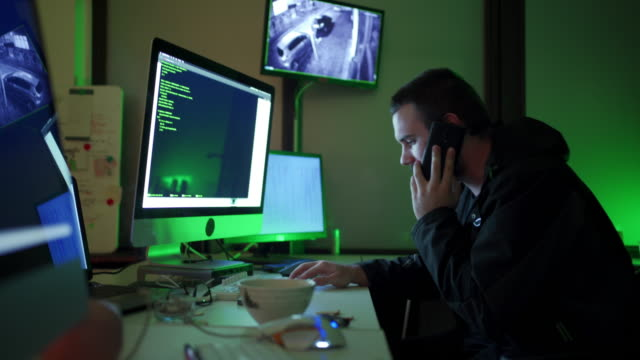 Hacker receiving instruction on mobile phone from his customer about program decoding Young computer programmer and hacker talking on the phone with customer fraud stock videos & royalty-free footage