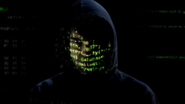ホログラムの顔に反映して、モニター上の碑文を精査ハッカー - 犯罪者点の映像素材/bロール