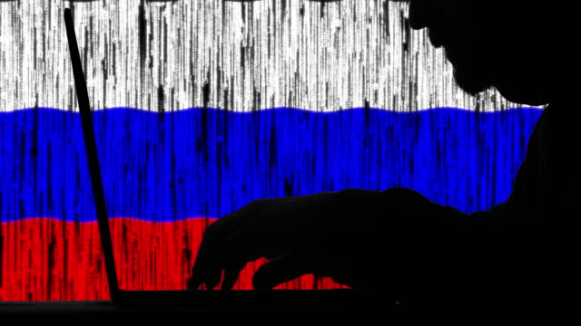 Hacker typing code on his laptop with Russian flag in background