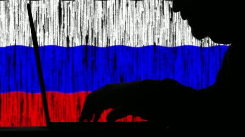 vídeos y material grabado en eventos de stock de hacker escribiendo código en su computadora portátil con la bandera rusa en segundo plano - rusia