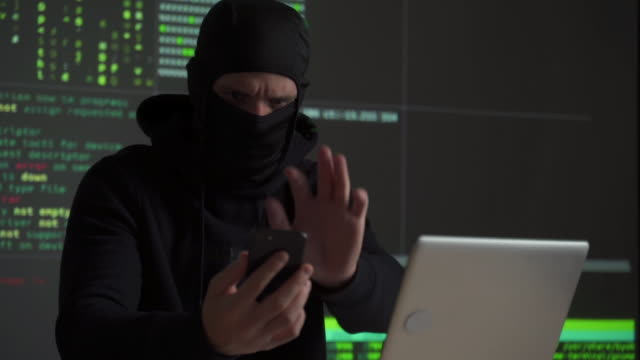 hacker uses a mobile phone to hack the system. stealing personal data and money from bank accounts. the concept of cyber crime and hacking electronic devices - spyware filmów i materiałów b-roll