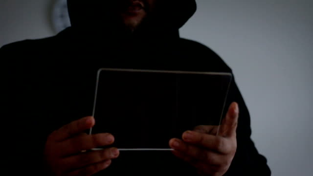 Hacker using blank clear glass tablet with dark tone and grain processed Hacker using blank clear glass tablet with dark tone and grain processed identity theft stock videos & royalty-free footage