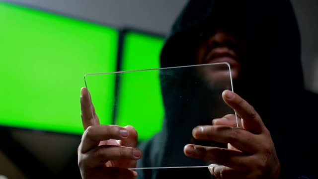 Hacker using clear glass tablet with green screen monitor behind and dark tone with grain processed Hacker using clear glass tablet with green screen monitor behind and dark tone with grain processed identity theft stock videos & royalty-free footage