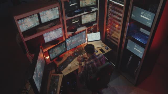 hacker using computer with multiple monitors - phishing filmów i materiałów b-roll