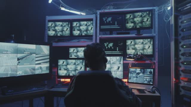 hacker beobachtet aufnahmen von überwachungskameras - überwachungskamera stock-videos und b-roll-filmmaterial