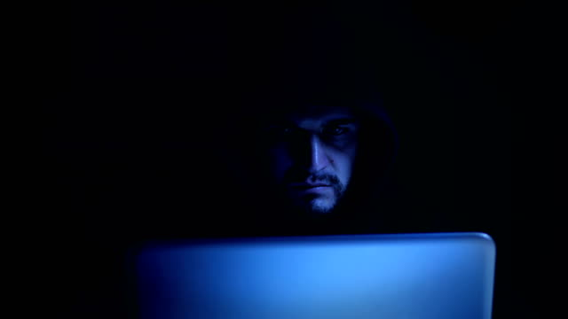 hacker with black hood types quickly on the computer at night hacker with black hood types quickly on the computer at night identity theft stock videos & royalty-free footage
