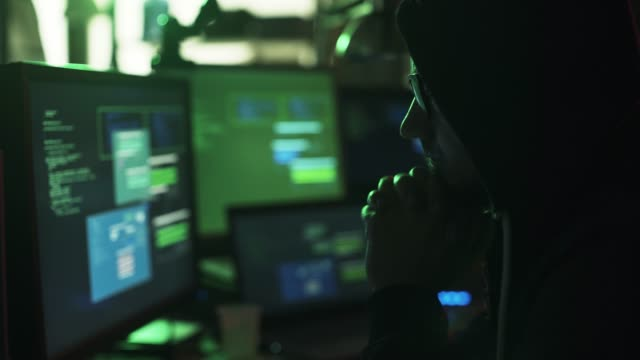Hacker with hoodie working with multiple screens and hacking systems