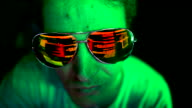 istock Hacker's glasses reflecting malicious code on screen. 1204824385