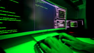 istock Hacker's hands on keyboard typing malicious code on large screen. 1204805559