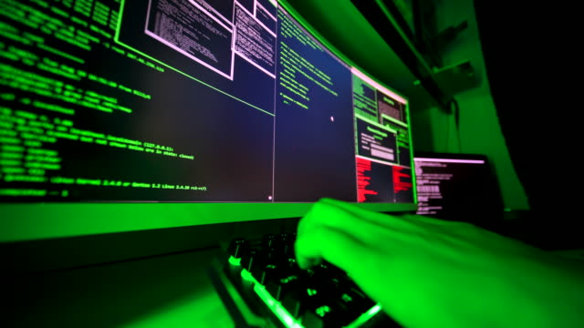 Hacker's hands typing malicious code into keyboard on large screen. A black-hat programmer hacking into illegal personal data. Coding ransomware attack to steal personal data in cyber attack. identity theft stock videos & royalty-free footage
