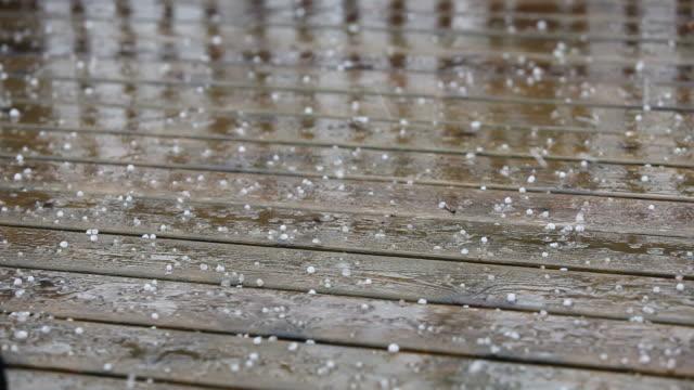 grandine e pioggia che cade su tavole di legno deck - grandine video stock e b–roll