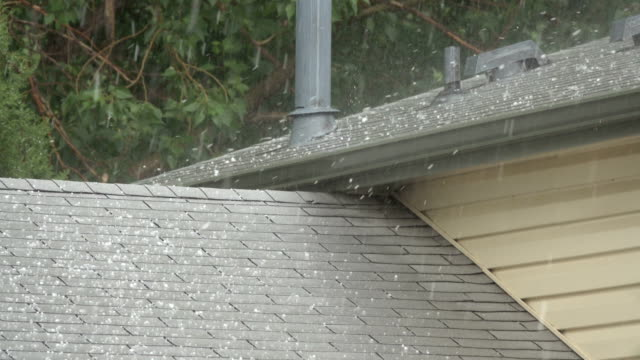 Hail falls on house roof shingles Denver Colorado heavy rain thunderstorm water