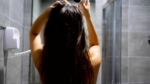 hair care girl holding in hand electric blow dryer and blowing on wet hair at bathroom of hotel room