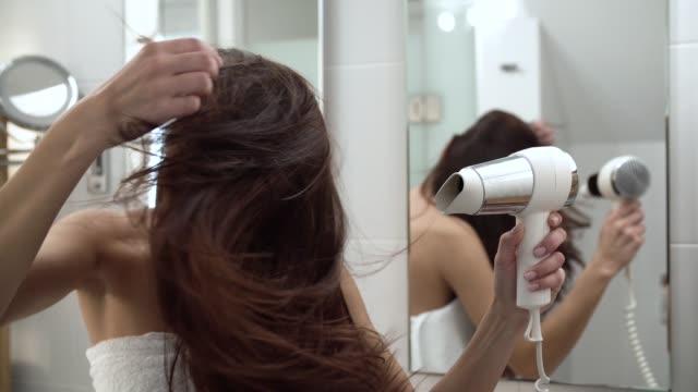 stockvideo's en b-roll-footage met haarverzorging. vrouw lange droogrek met haardroger in de badkamer - hair woman