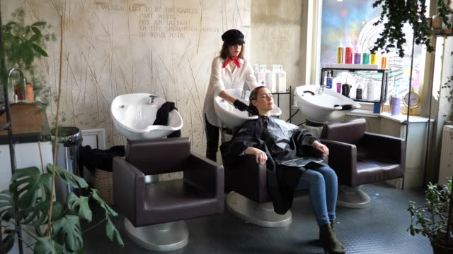 Hair dresser is rinsing hair to the customer Young millennial woman at hair stylist small business saturday stock videos & royalty-free footage
