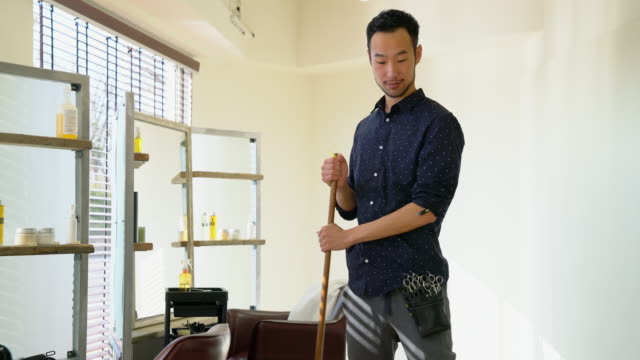 hair dresser sweeping up in his salon - hairdresser filmów i materiałów b-roll