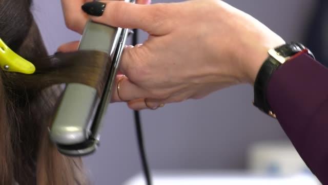 stockvideo's en b-roll-footage met haar ijzer straightening beauty care salon spa. haar rechttrekken. stijltang en kam. - curly brown hair