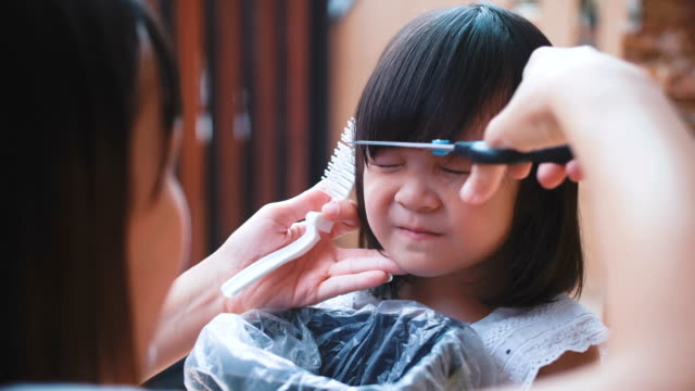 Haircut Asian little girl is cut her hair by mother hairstyle stock videos & royalty-free footage