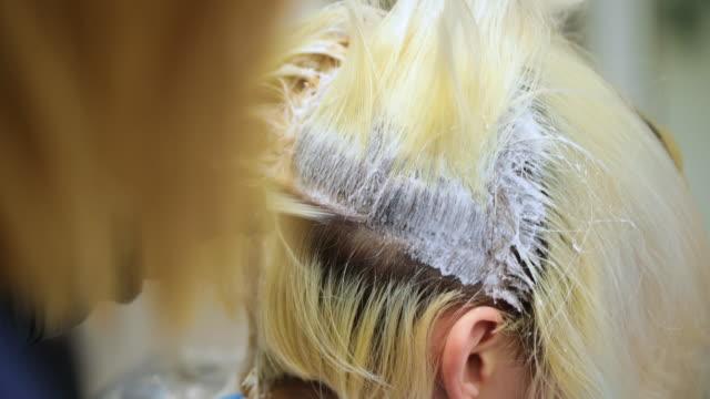 friseur anwendung haarfärbemittel auf blonde haare - haartönung stock-videos und b-roll-filmmaterial