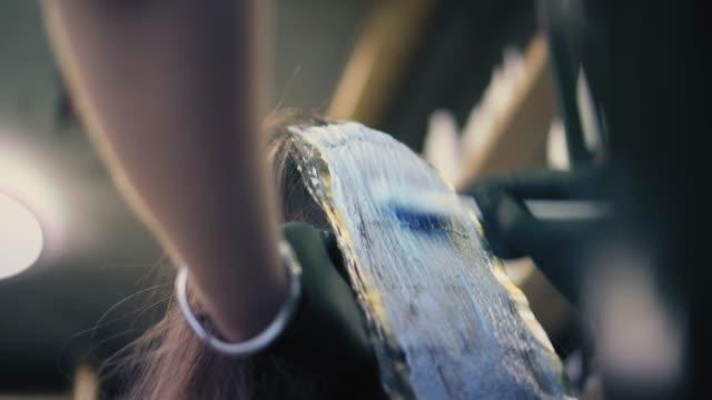 Aplicar tinte de pelo peluquería en filamentos de pelo y wraping de mujer en papel de aluminio - vídeo