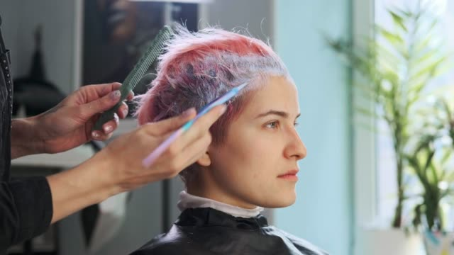 Hairdresser colorist puts paint on hair of woman client. Hairdresser colorist puts paint on hair of woman client. Discoloration in the salon. highlights hair stock videos & royalty-free footage
