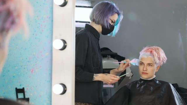 vidéos et rushes de le coloriste de coiffeur met la peinture sur le cheveu du client de femme. - salons et coiffeurs