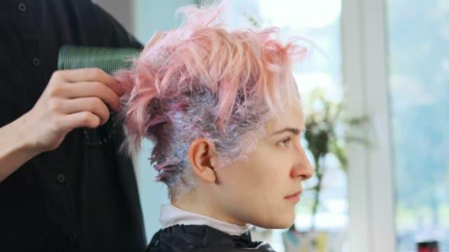 stockvideo's en b-roll-footage met de colorist van de kapper zet verf op haar van vrouwencliënt. - roze haar