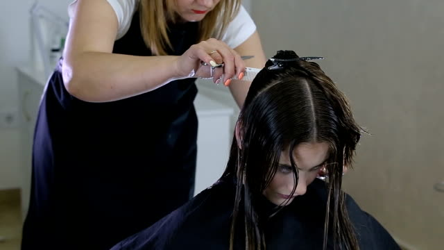 hairdresser combing and cuting hair of teen girl client in hair salon - bleach stock videos & royalty-free footage