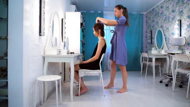 Peluquería, peinar el cabello de una hermosa joven morena - vídeo
