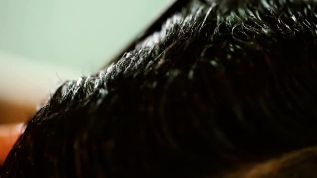 parrucchiere unendo i capelli del cliente - bassino video stock e b–roll
