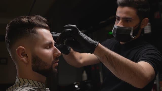 vídeos de stock e filmes b-roll de hairdresser correcting shape of brows for male client - sobrancelha