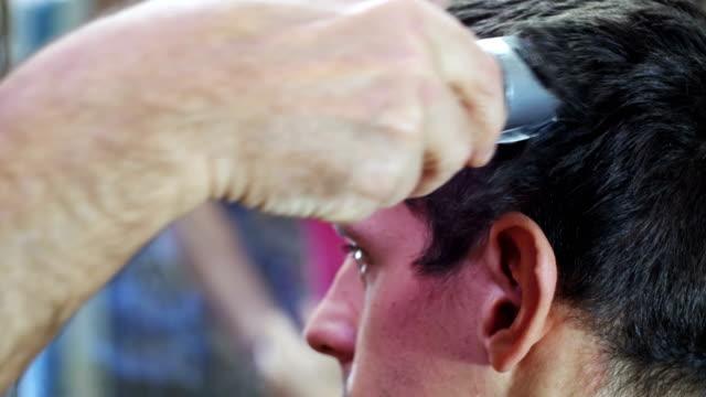 vidéos et rushes de coiffeur coupe les cheveux d'un jeune homme avec clipper à la maison - salons et coiffeurs