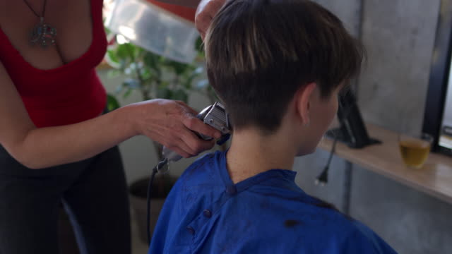 Hairdresser cutting female client with electric razor