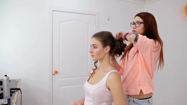 Hairdresser finishing hairstyle for young pretty woman video