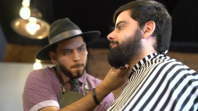 Hairdresser grooming man's beard with scissors video