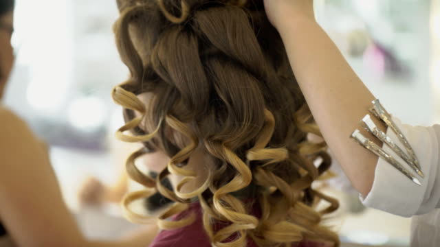 Hairdresser makes curls for woman and artist applies makeup on face