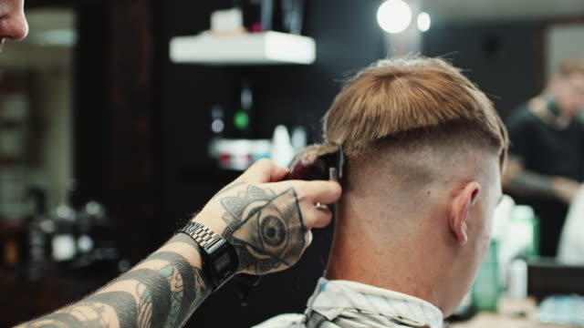 Hairdresser makes haircut to the client