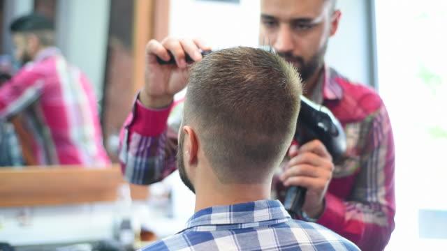 vidéos et rushes de salon de coiffure fait coiffure hipsters barbu souriant avec un sèche-cheveux - salons et coiffeurs