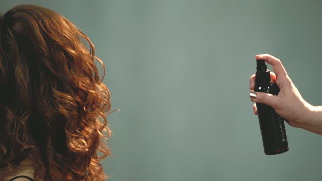 stockvideo's en b-roll-footage met kapper persen spray knop, van waaruit de lak spatten op rood haar. - curly brown hair