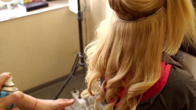 Hairdresser spray hair spray on the girl's hair. video