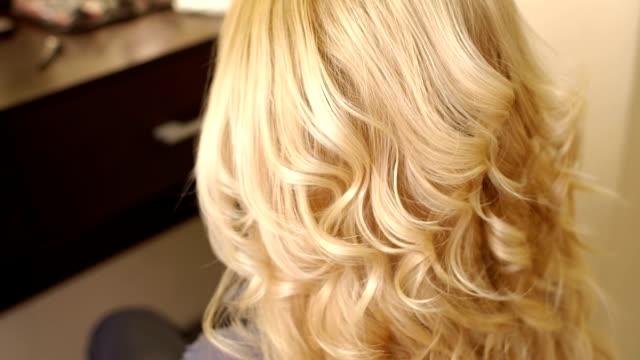 stockvideo's en b-roll-footage met kapper spray haarlak op haar van het meisje. - blond curly hair