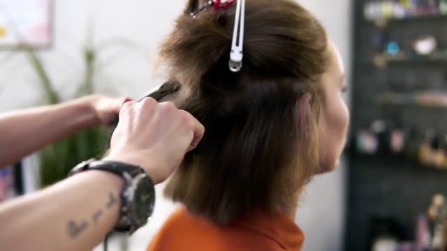 kuaför saç saç demir güzellik studio ile oturan kadının düzeltiyor. o özel cihaz elinde tutan ve hafifçe kısa sarı saçlı üstten yukarıdan aşağıya doğru hareket eder - demir stok videoları ve detay görüntü çekimi