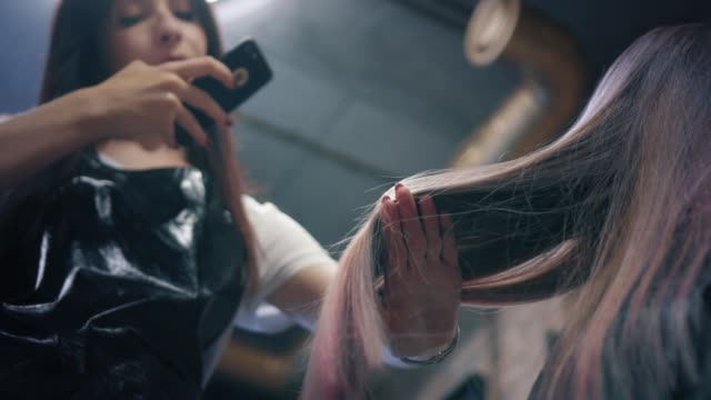 美容室は、ヘアサロンでのスマート フォンの女性の長い髪の写真を撮る。美容師は彼女の仕事を賞賛し、染め髪のストランドを示しています。ダウンの角度。遅い mo - 美容室のビデオ点の映像素材/bロール