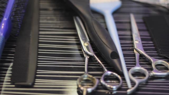 hairdresser tools. comb scissors and brushes laid out on the workspace - narzędzie do pracy filmów i materiałów b-roll